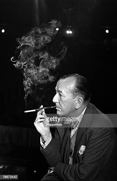 1951 English dramatist actor and composer Noel Coward is pictured smoking a cigarette from a cigarette holder as he rehearses for his play 'Relative...