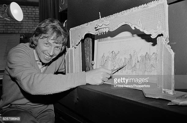 English entertainer and singer Tommy Steele pictured with a model of a theatre stage set and backdrop in London on 14th March 1979