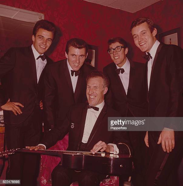 English entertainer and television presenter Bruce Forsyth posed backstage with pop group The Shadows in London in 1964 From left to right John...