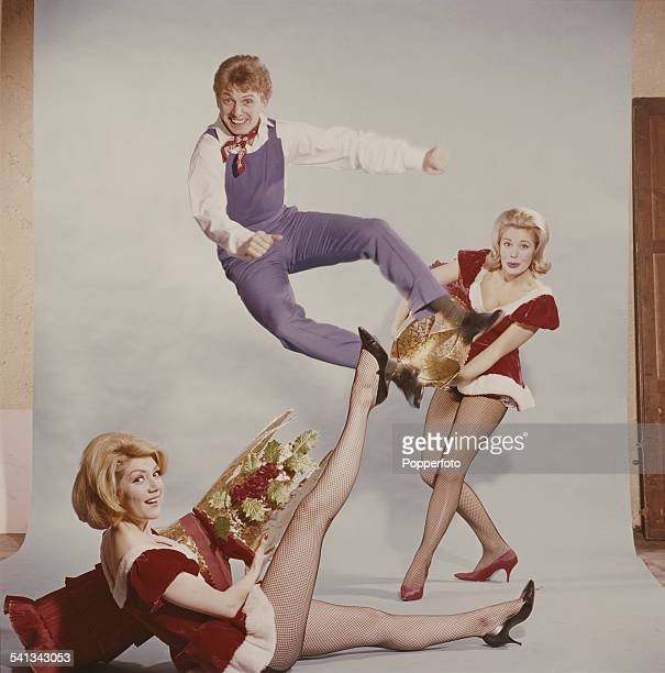 English entertainer Tommy Steele jumps out of an oversized christmas cracker pulled by two young women in festive costume in 1962