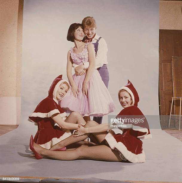 English entertainer Tommy Steele pictured with his arms around the waist of a young girl with two young women wearing festive costume sitting at...