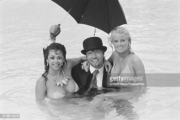 English entrepreneur and businessman Richard Branson pictured wearing a business suit and bowler hat whilst holding an umbrella with two female...
