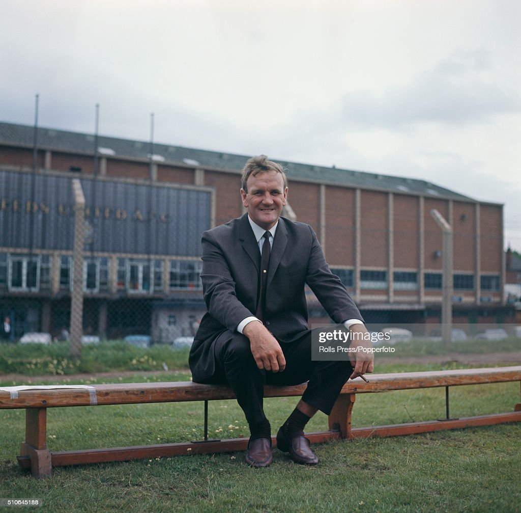 English ex footballer and manager of Leeds United Don Revie pictured sitting on a bench and smoking a cigar outside Leeds United's Elland Road...