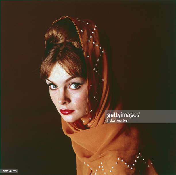English fashion model Jean Shrimpton poses looking at the camera with a pumpkincolored beaded scarf wrapped around her bouffant hairdo 1960s