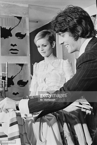 English fashion model Twiggy and her boyfriend and manager Justin de Villeneuve look over some of the items in Twiggy's own 'Twiggy Dresses' line of...