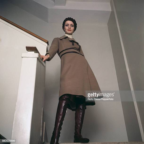 English fashion model Twiggy pictured wearing a knee length light brown or taupe coat with brown leather boots and beret whilst standing on stairs in...
