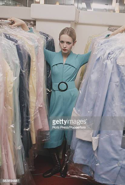English fashion model Twiggy pictured wearing a turquoise blue knee length one piece play suit as she stands between two rails of clothes in the...