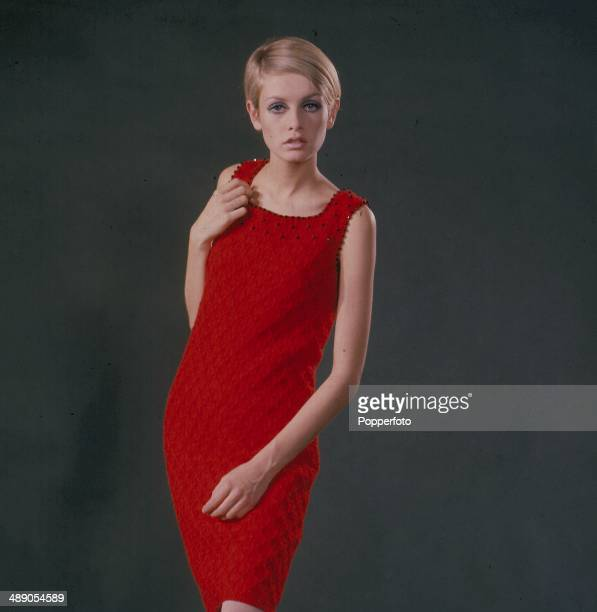 English fashion model Twiggy stands wearing a red sleeveless cocktail dress in 1967