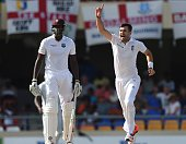 English fast bowler James Anderson celebrates beside West Indies batsman Jason Holder after becoming the highest ever English wicket taker with 384...