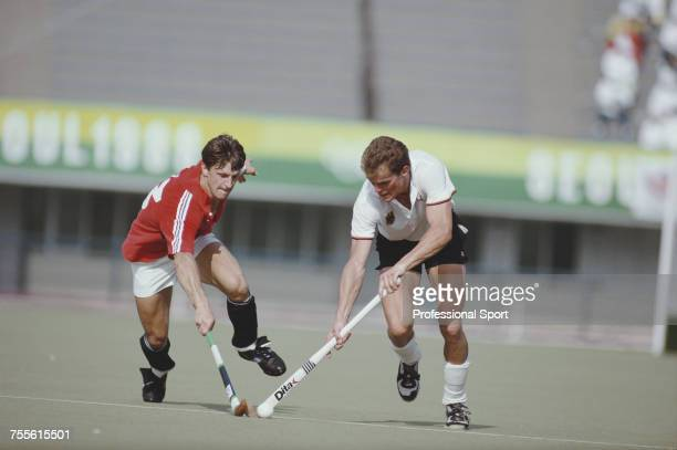 English field hockey player Sean Kerly of the Great Britain team pictured left in action fighting with a West Germany player for the ball during play...