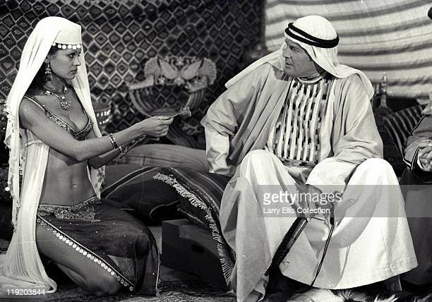 English film actor Roger Moore wearing a keffiyeh as James Bond in the film 'The Spy Who Loved Me' 1976 In this scene actress Dawn Rodrigues presents...