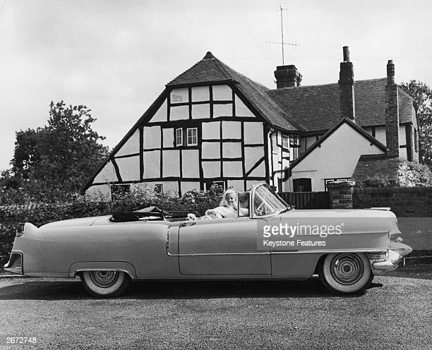 English film actress Diana Dors at the wheel of her Cadillac convertible outside her halftimbered 15th century home in Sussex