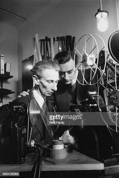 English film director David Lean working with a film editor during production of his film adaptation of 'Oliver Twist' Pinewood Studios...