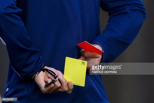 English football referee Howard Webb keeps a red and a yellow card behind him during a seminar for 2014 FIFA World Cup referees on March 27 2014 at...