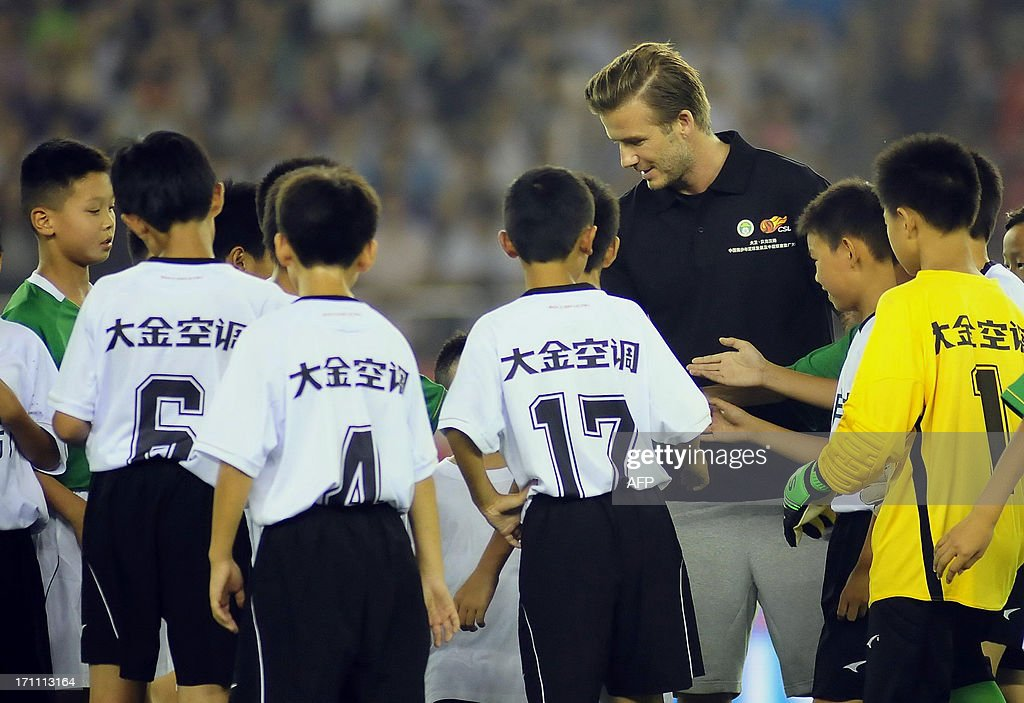 English football superstar David Beckham shakes hands with young players during a China Super League match between Hangzhou Greentown and Beijing Guoan in Hangzhou, east China's Zhejiang province on June 22, 2013. Beckham on June 21 sent his love to people hurt in a stampede at a Shanghai event, as fans praised him despite the incident. CHINA