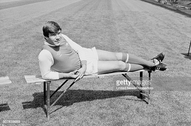 English footballer and forward for Arsenal Malcolm Macdonald posed lying on a bench on the pitch at Highbury stadium in London on 17th July 1979