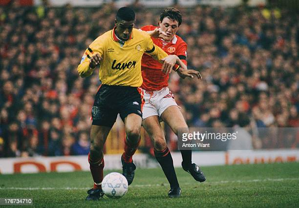 English footballer Brian Deane of Sheffield United fends off Steve Bruce of Manchester United during an English Premier League match at Old Trafford...