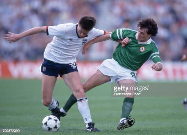 English footballer Chris Waddle is tackled for the ball by Scottish born footballer Ray Houghton during play in the group 2 match between England and...