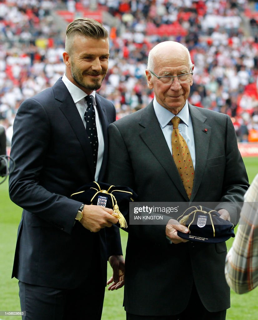 English footballer David Beckham (L) and Sir Bobby Charlton are presented on June 2, 2012 with a cap to recognize players who have played over 100 international matches during an international friendly football match between England and Belgium at Wembley Stadium in London. AFP PHOTO/IAN KINGTON USE
