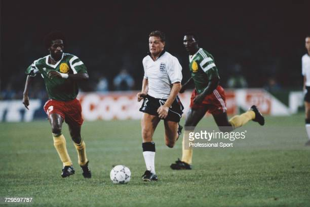 English footballer Paul Gascoigne makes a run with the ball as Cameroon midfielder JeanClaude Pagal prepares to make a tackle in the quarter final...