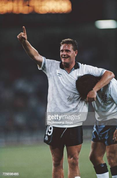 English footballer Paul Gascoigne raises one arm in the air as he hugs a teammate during play in the quarter final match between Cameroon and England...