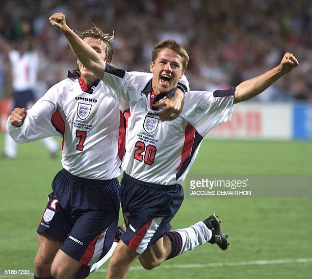 English forward Michael Owen jubilates with teammate David Beckham after scoring the 11 equalizer 22 June at Toulouse stadium during the 1998 Soccer...