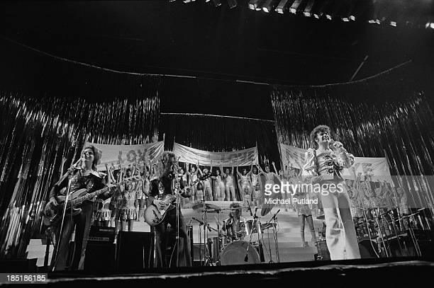 English glam rock singer Gary Glitter performing with the Glitter Band and a large chorus of young women at the Rainbow Theatre London November 1973...