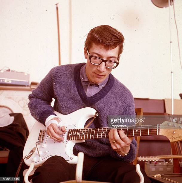 English guitarist Hank Marvin of The Shadows plays a white Fender Stratocaster guitar backstage in England in 1963