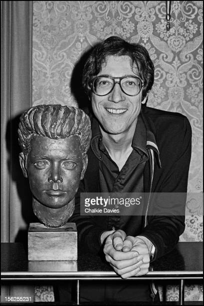 English guitarist Hank Marvin poses next to a wooden bust of Cliff Richard at his manager's office London 1977