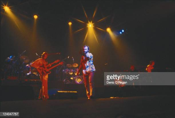 English guitarist Mike Rutherford and singer Phil Collins perform with rock band Genesis circa 1977