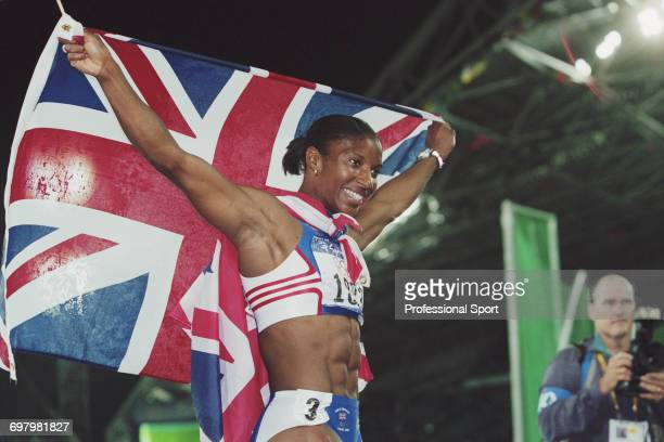 English heptathlete Denise Lewis pictured holding a union jack flag in celebration after finishing in first place to win the gold medal for Great...