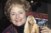 English hostess Cynthia Payne holds a copy of the erotic magazine 'Men's Collection' in London circa 1987