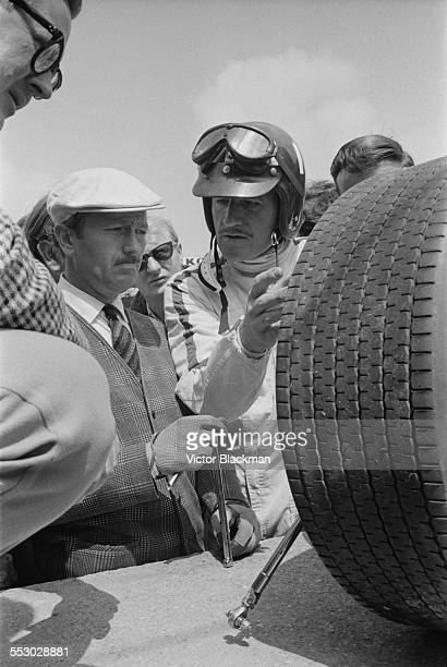 English inventor engineer and founder of Lotus Cars Colin Chapman with British racing driver Graham Hill at the Silverstone Circuit 14th July 1967