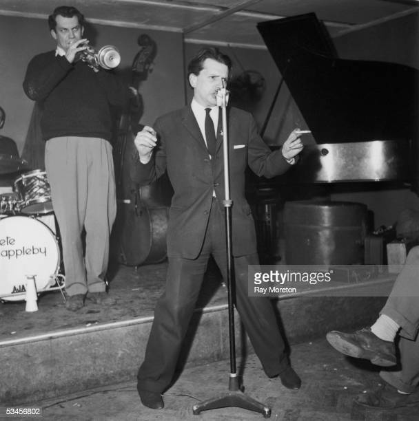 English jazz singer and writer George Melly singing with trumpeter Mick Mulligan and his jazz band in a London nightclub April 1960