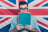 English language learning concept-portrait of excited man holding colorful copy books in hands closing half face with notebooks standing over English flag background