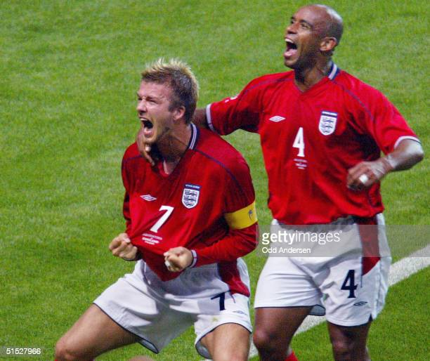 English midfielder David Beckham and his teammate defender Trevor Sinclair jubilate after David Beckham scored a goal during the Group F first round...