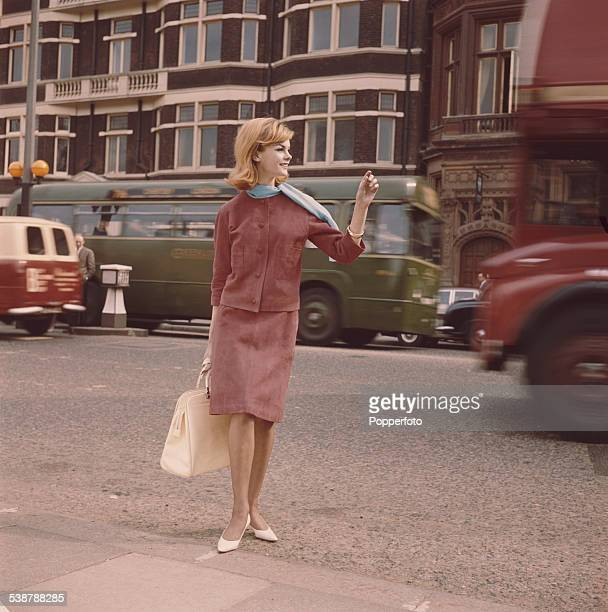 English model and actress Jean Shrimpton pictured wearing a red suede jacket and skirt and light blue scarf whilst crossing a London street in 1962