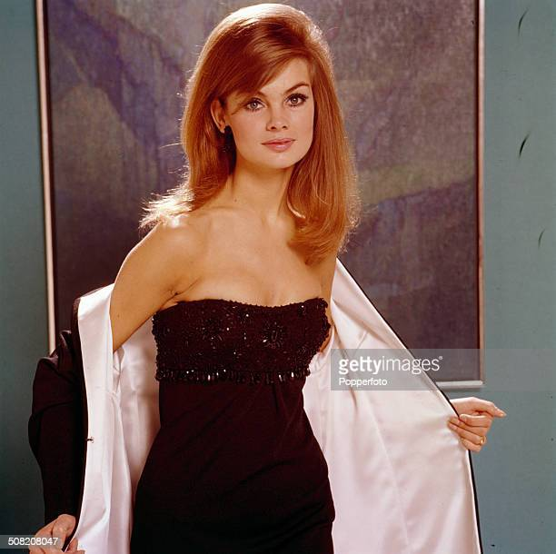 English model and actress Jean Shrimpton posed wearing a white lined long black jacket over a black strapless evening dress in 1965