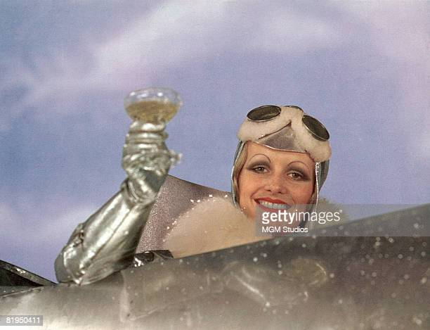 English model and actress Twiggy as Polly Browne raises a champagne glass in the cockpit of an aeroplane in a scene from the fim version of Sandy...