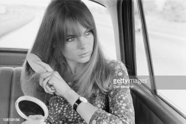 English model Jean Shrimpton spruces herself up in the back of a car 12th July 1966