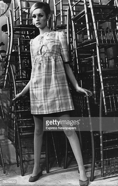 English model Twiggy originally Lesley Hornby poses in font of a stack of chairs Original Publication People Disc HW0066