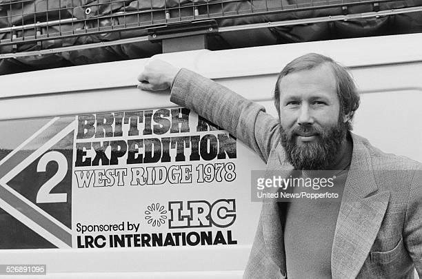 English mountaineer Chris Bonnington pictured standing beside a van publicising the expedition to climb the west face of the mountain K2 outside the...