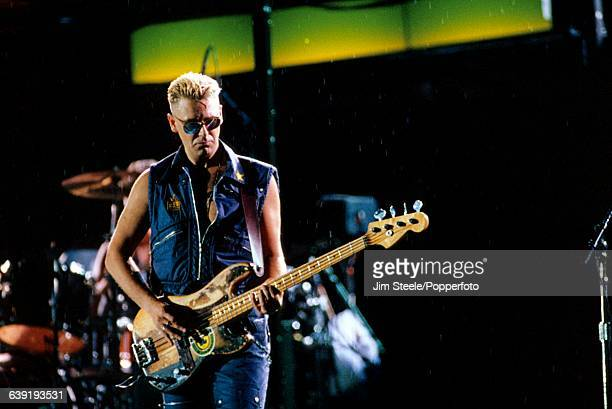 English musician and bass guitarist with U2 Adam Clayton performs live on stage during the band's Zoo TV Zooropa tour at Wembley Stadium in London...