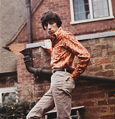English musician and bass player with The Rolling Stones Bill Wyman posed beside a wall circa 1967