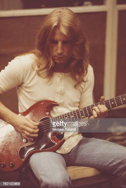 English musician and guitarist with rock group Status Quo Rick Parfitt pictured playing a Gibson SG guitar during a recording session in London on...