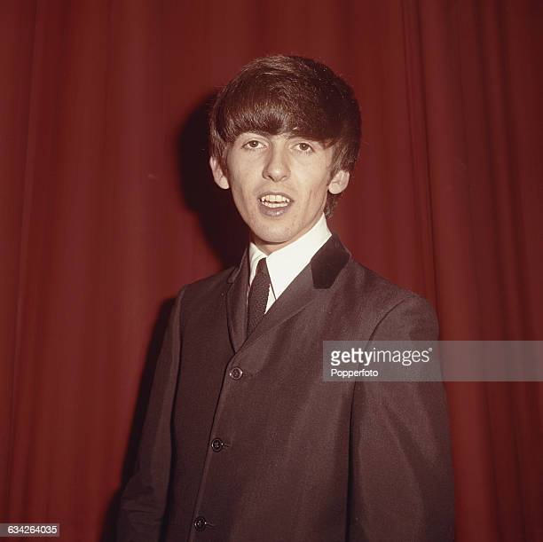 English musician and guitarist with The Beatles George Harrison posed backstage at a venue during the band's autumn tour of the United Kingdom in 1963