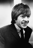 English musician and guitarist with the Rolling Stones Brian Jones pictured wearing a jacket and tie in 1963