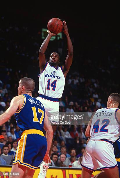 J English of the Washington Bullets goes up to shoot over Chris Mullin of the Golden State Warriors during an NBA basketball game circa 1991 at the...