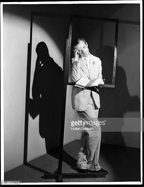 English photographer and set designer Cecil Beaton leans against a frame on a stand while reading a book