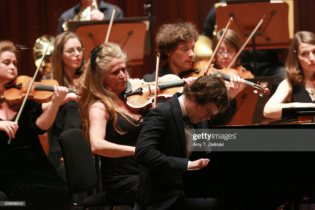 English pianist Benjamin Grosvenor directs while playing the piano the Britten Sinfonia with violinist Jacqueline Shave beside him in a performance of Mozart's last piano concerto at Milton Court Concert Hall on May 1, 2016 in London, England.